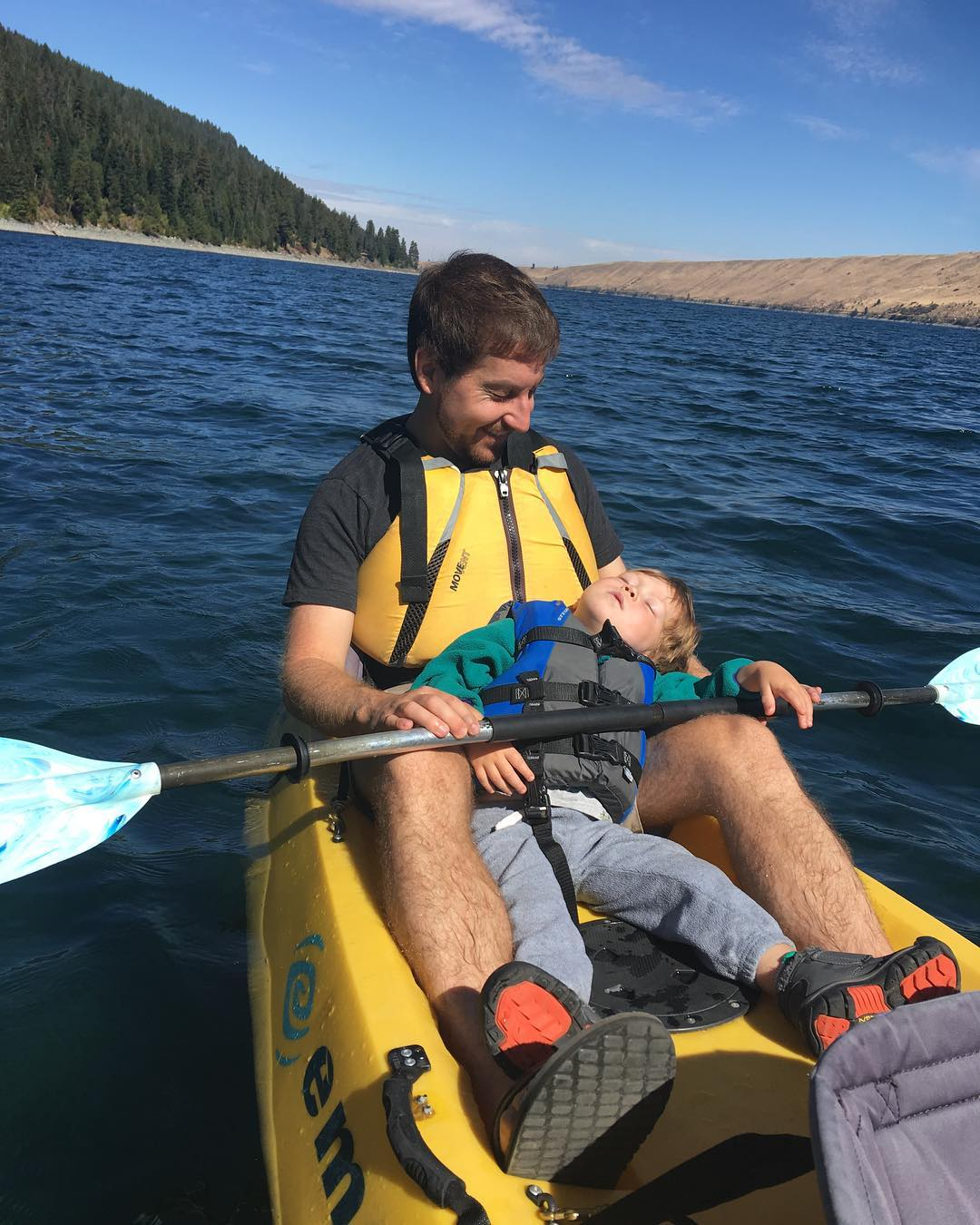 Charlie sleeping in Daniel's arms in the kayak.